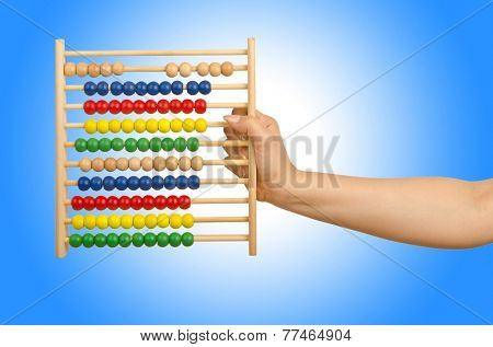 Hand holding abacus on white