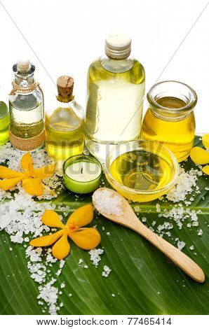 spa supplies with orchid, oil, candle ,soap ,salt in spoon,on banana leaf