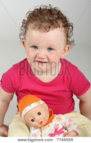 Baby girl with her doll on grey background