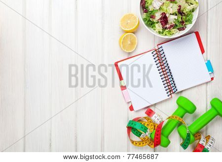 Dumbells, tape measure, healthy food and notepad for copy space. Fitness and health