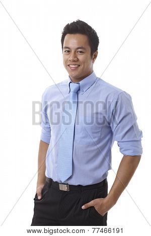 Handsome young Asian businessman smiling with hands in pockets, wearing shirt and tie.