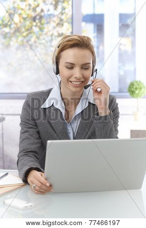Portrait of pretty young dispatcher working , using laptop computer, wearing headphones, smiling.