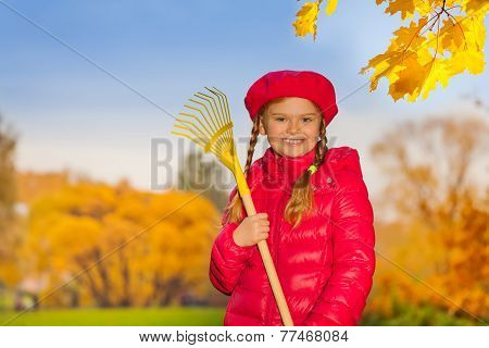 Portrait of beautiful smiling girl with rake