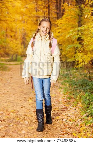 Beautiful girl with rucksack stands in forest