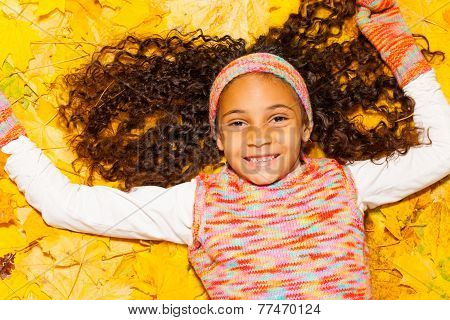 Happy black girl with curly hair in autumn leaves