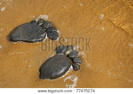 pair trace feet made of a pebble stone on the sea sand  texture surface backdrop