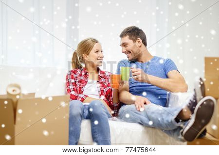 repair, moving, resting in and people concept - smiling couple holding cups drinking tea or coffee at new home