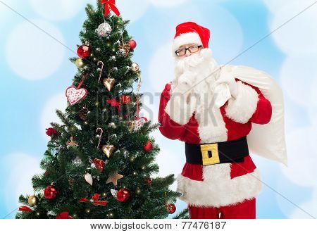 christmas, holidays and people concept - man in costume of santa claus with bag and christmas tree making hush gesture over blue lights background