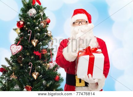 christmas, holidays and people concept - man in costume of santa claus with gift box and tree making hush gesture over blue lights background