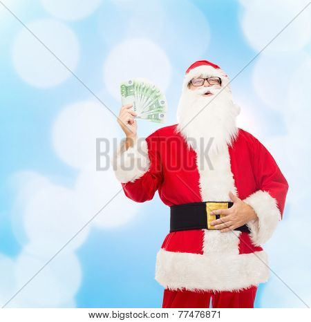 christmas, holidays, winning, currency and people concept - man in costume of santa claus with euro money over blue lights background