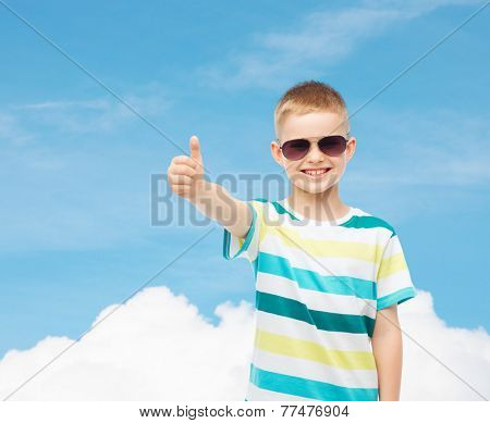 happiness, summer, childhood, gesture and people concept - smiling cute little boy in sunglasses over blue sky background showing thumbs up