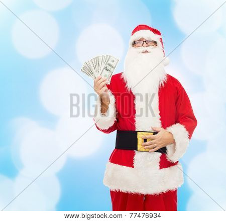 christmas, holidays, winning, currency and people concept - man in costume of santa claus with dollar money over blue lights background