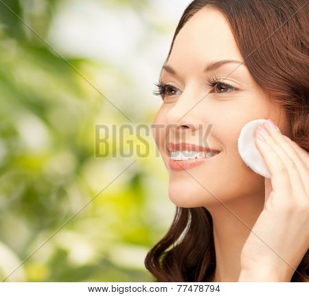 beauty, people and health concept - beautiful smiling woman cleaning face skin with cotton pad over green background