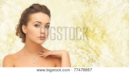 beauty, holidays, people and jewelry concept - woman wearing shiny diamond pendant over yellow lights background