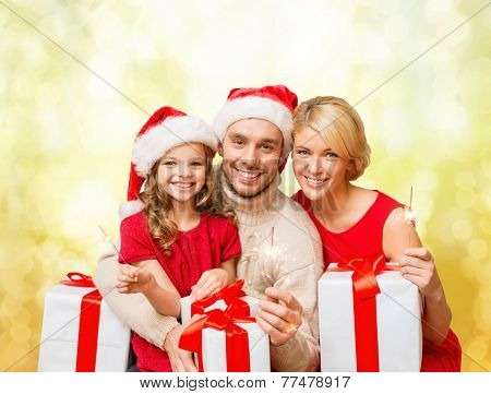 family, christmas, xmas, happiness and people concept - smiling family in santa helper hats with many gift boxes and bengal lights