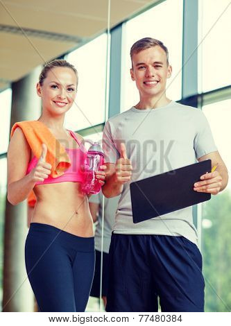 fitness, sport, exercising and diet concept - smiling young woman with personal trainer after training in gym showing thumb up