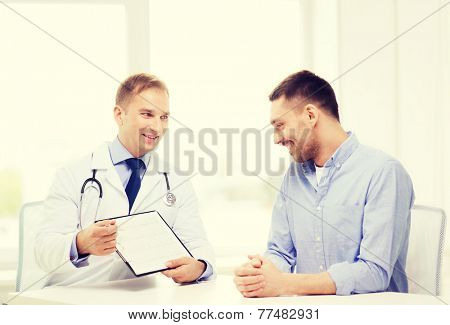 healthcare and medicine concept - smiling doctor with clipboard and patient in hospital