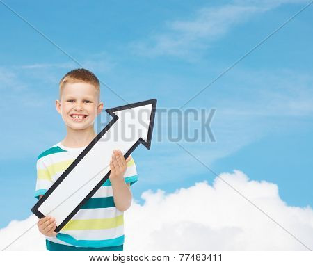 advertising, direction and childhood concept - smiling little boy with white blank arrow pointing up over blue sky