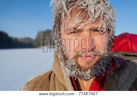 Portrait of the young man with frozen icy hairs on head and beard