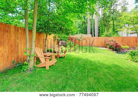 Fenced Backyard With Green Lawn And Sitting Area