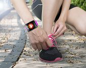 image of personal assistant  - human hand tying shoelaces wearing bright pink watchband touchscreen smartwatch with red health icon on forest trail background - JPG