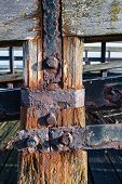 pic of neglect  - Part of a neglected wooden jetty with rusted iron from close - JPG