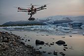 pic of iceberg  - A drone with raised landing gears and a camera flying over icebergs with a glacier in the background - JPG