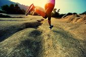 stock photo of country girl  - young woman runner legs running on mountain trail - JPG