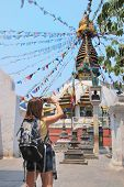 Tourist With Camera In Front Of Budhist Stupa poster