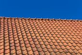 picture of red roof  - Red roof tile pattern over blue sky