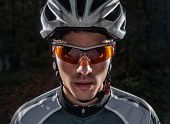 stock photo of flashing  - Cyclist portrait with flash light in a forest outdoors - JPG