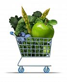stock photo of grocery cart  - Healthy shopping as a supermarket cart filled with green fresh vegetables as and fruit as a health food symbol for living well by buying market produce on a white background - JPG