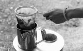 foto of hot-water-bag  - seller hand holding the coffee bag for filtering coffee to the metal container - JPG