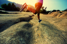 picture of crossed legs  - young woman runner legs running on mountain trail - JPG