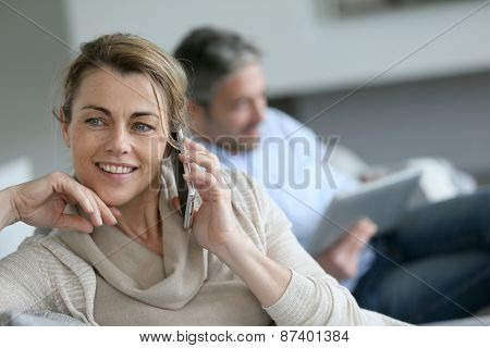 Mature woman talking on smartphone, husband using tablet