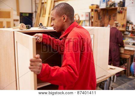 Apprentice Building Furniture In Carpentry Workshop