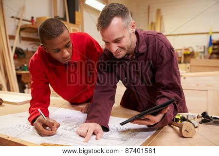 Carpenter With Apprentice Looking At Plans In Workshop