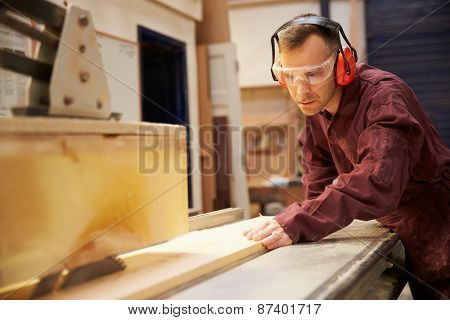 Carpenter Using Circular Saw In Carpentry Workshop