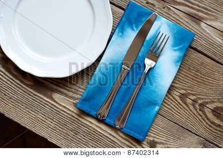 Empty plate on wooden tabletop with tablecloth close up