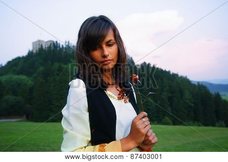 A beautiful girl in historical costume in a wild meadow landscape holding a secretful romantic rose