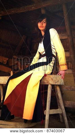 beautiful girl in a historical costume sitting on a wooden bench inside a forest cabin