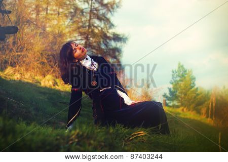 A beautiful young woman with dark hair and a historical dress posing on a meadow in open lanscape