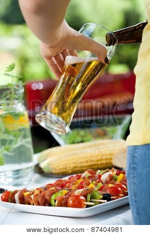 Woman Pouring Beer On Barbecue
