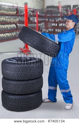 Mechanic Piling Up Tires In The Workshop