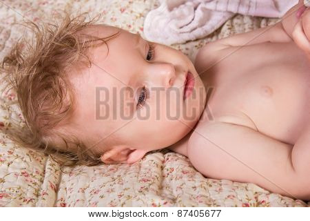 Cute blonde baby girl with beautiful blue eyes lying on bed with toy