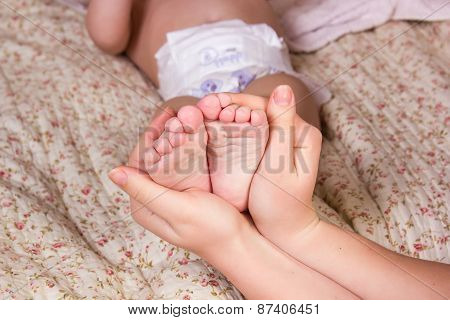 Mother gently hold baby leg in hand. Beautiful color image with soft focus on baby foot