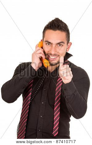 closeup portrait of handsome hispanic man talking on corded retro phone