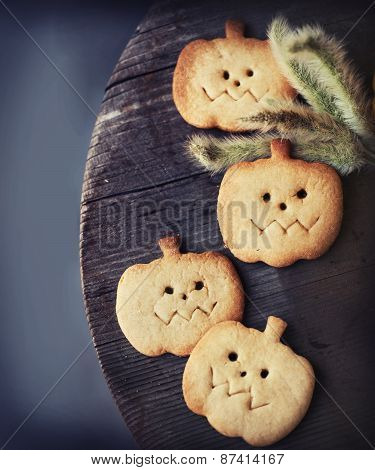 Halloween homemade gingerbread cookie in pumpkin shape over wooden background
