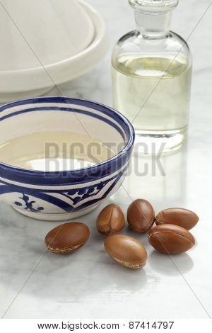 Cup with argan oil and nuts for cosmetics