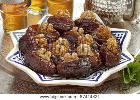 Dish with preserved ripe Medjool dates stuffed with walnuts for festive occasions